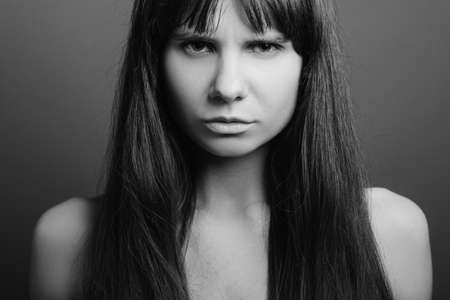 Distrustful looking beautiful girl. Insecure facial expression. Black and white closeup portrait of emotional lady.