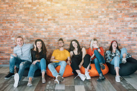 Millennials che vanno in giro nella zona lounge. Giovani che riposano in sacchi di fagioli, si divertono insieme, si godono la pausa al lavoro. Archivio Fotografico