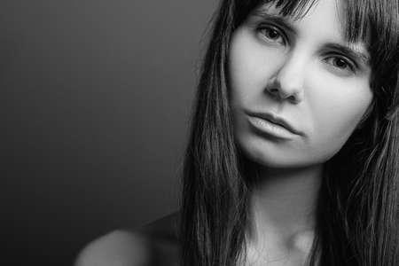 Ontgoocheld mooi meisje. Wantrouwende gezichtsuitdrukking. Zwart-wit close-up portret van emotionele dame. Ruimte kopiëren.