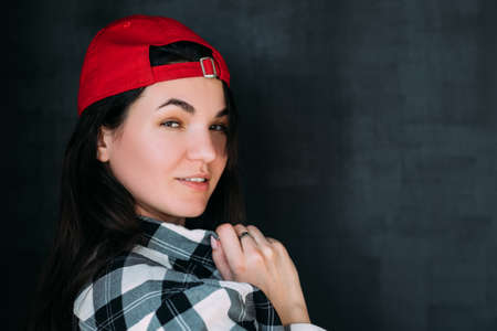 Closeup portrait of millennial lady in checked shirt and red baseball cap. Emotional woman posing with flirty facial expression.