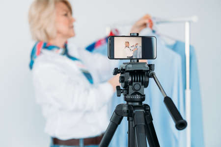 Personal blog. Smartphone on tripod. Busy female on screen. Clothes showroom business. Fashion consultant advice.