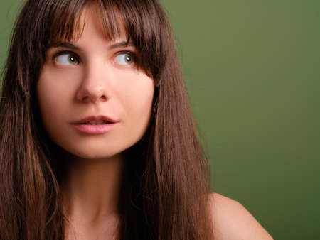 Surprised cute young lady. Interested facial expression. Closeup portrait of emotional brunette girl.