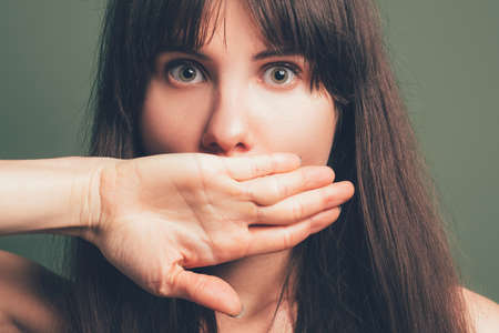 Impressed young pretty lady. Frightened facial expression. Closeup portrait of emotional brunette girl covering mouth with hand. Stock Photo