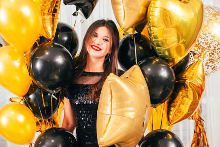 Special day. Portrait of brunette lady standing with bunch of golden and black balloons. Happy facial expression.