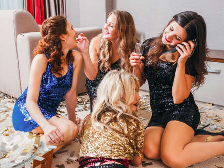 Hen party celebration. Fun leisure. Girls in dresses fooling around on floor. Drunk lady talking on shoe instead of phone. Stock Photo
