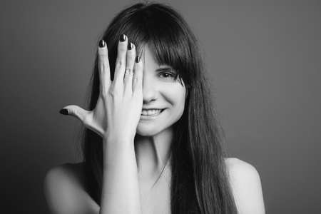 Joyful sweet girl. Amused facial expression. Black and white closeup portrait of emotional lady smiling, covering eye with hand. Banco de Imagens