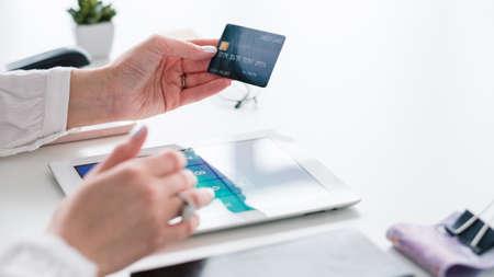 Online-Banking. Kreditkarten Zahlung. Tablet auf dem Schreibtisch. Plastikgeld in der Hand. Frau, die Transaktion macht. E-Zahlung. Standard-Bild