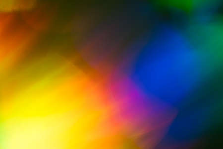 Blurred lens flare lights. Defocused dark abstract background. Glowing effect. Фото со стока