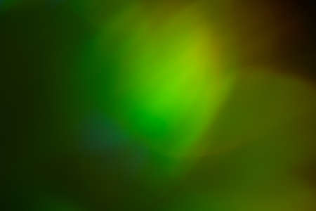 Blurred green and yellow lights. Bokeh abstract background with lens flare glow effect.