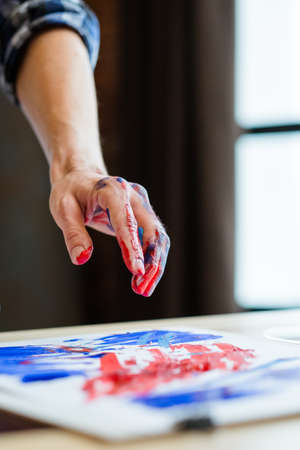 Contemporary art school. Closeup of male left hand dirty with red and blue acrylic paint over blurred finger painting.