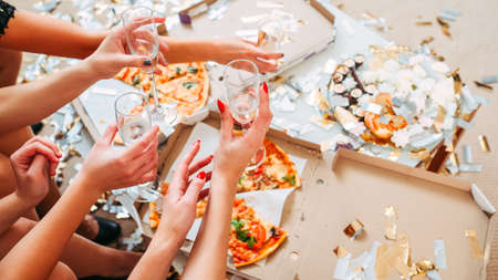 Girls fun party over. Cropped shot of ladies putting glasses on table with pizza leftovers, finishing celebration.