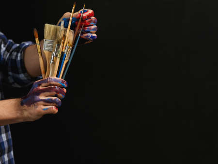Art and creativity. Painter essential tools. Cropped shot of man picking out brush from bunch over dark background.