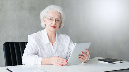 Successful business woman. Head of department. Portrait of confident senior lady sitting at desk, holding tablet.