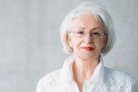 Successful business woman. Closeup of intelligent senior lady in eye glasses, white blouse. Confident facial expression.