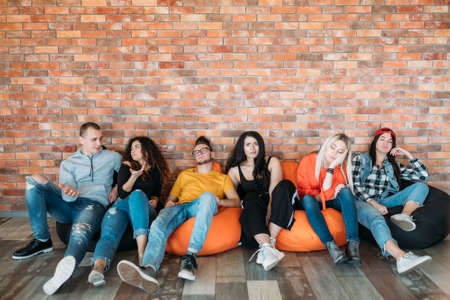 Diverse group of millennials sitting on bean bags. Bored and annoyed. Tired of dull presentation, bad film, empty talk.