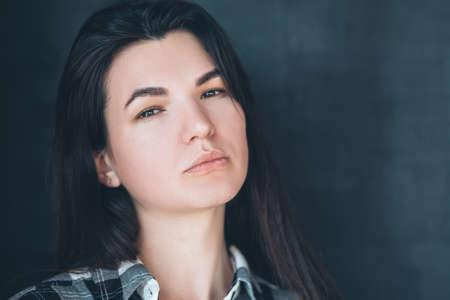 Serious young brunette. Millennial portrait. Suspicion doubt mistrust. High personal opinion. Youth arrogance. Unhappy