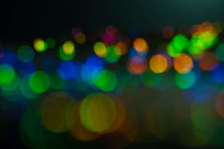 Blurred multicolor bokeh circles on dark background. Defocused lens flare glow. Abstract design. 스톡 콘텐츠