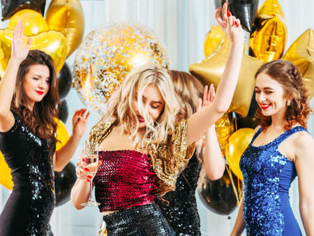 Fancy party. Festive event. Pretty girls dancing in sparkling dresses, enjoying celebration at home decorated with balloons.