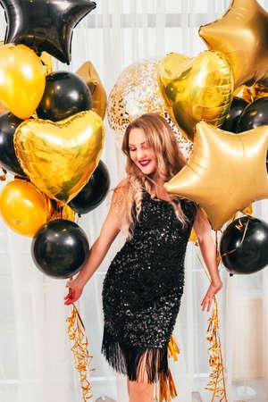 Mädchen Party. Besonderen Anlass. Schöne Dame im schwarzen funkelnden Kleid lächelnd, mit Luftballons über weißen Vorhängen stehend.