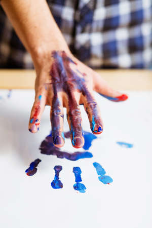 Contemporary art trend. Creative hobby and fun leisure. Closeup of male hand dirty with paint leaving print on white paper. Reklamní fotografie - 121221515