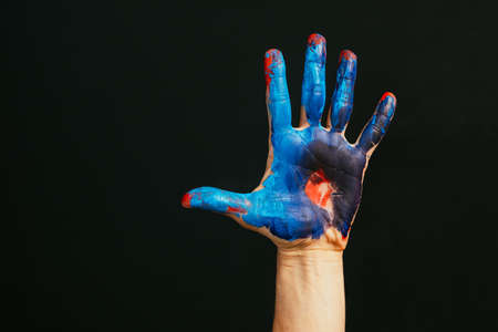 Modern art school. Master class. Creativity and inspiration. Closeup of male hand dirty with paint. Dark background empty space.