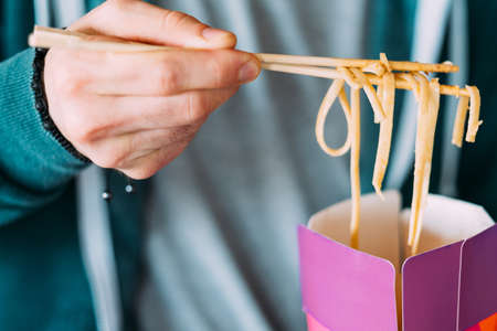 Takeaway fast food. Closeup of male hand holding asian noodles on chopsticks. Millennials modern lunch. Meal delivery service.