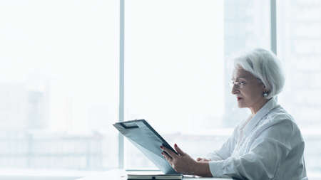 Successful business woman. Corporate lifestyle. Side view of senior lady sitting with papers at office desk against big window.