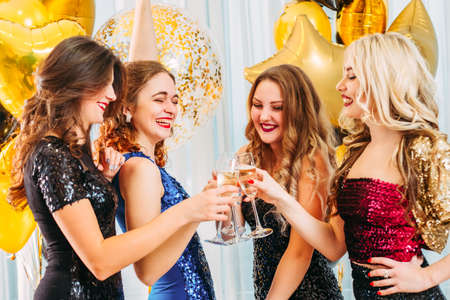 Fancy party. Festive occasion. Ladies in sequin dresses. Happy girls clinking glasses with champagne, laughing, having fun.