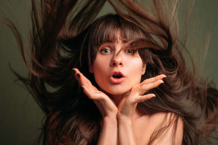 Amazed pretty girl. Closeup portrait of young brunette lady with long flying hair and bangs. Beauty care. 写真素材