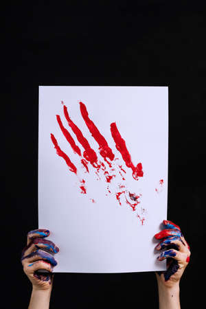 Creative hobby and inspiration. Contemporary artwork over dark background. Acrylic painting of red abstract hand print.