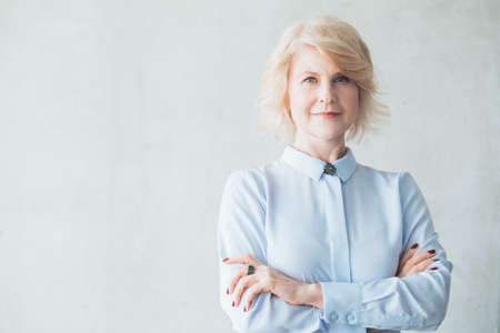 Successful business woman. Smart, intelligent female leader. Portrait of blonde mature lady standing with arms folded. 写真素材