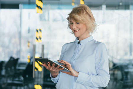 Modern business woman lifestyle. Successful career. Portrait of mature blond lady using tablet for work, smiling.