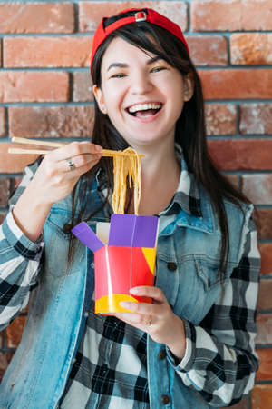 Youth eating habit. Takeout food. Excited female millennial with Chinese noodles. Yummy spicy meal, unhealthy nutrition.