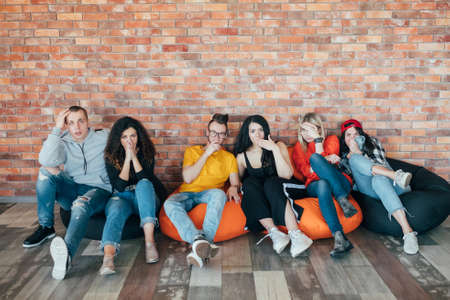 Diverse group of millennials sitting on bean bags. Shock and disgust on faces. Hands covering mouths. Negative emotion. Foto de archivo - 121283446