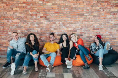 Millennials che si rilassano nella zona del tempo libero dopo una dura giornata di lavoro. I giovani seduti in poltrona a cuscino, ridendo.