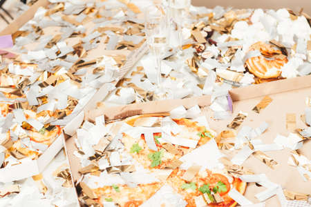 After party mess. Closeup of pizza, doughnut leftovers covered with shiny confetti. Half empty champagne glasses.