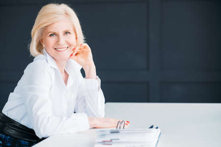 Smiling business woman at workplace. Time for break. Aged lady sitting looking at camera. Hand at cheek. Copy space.