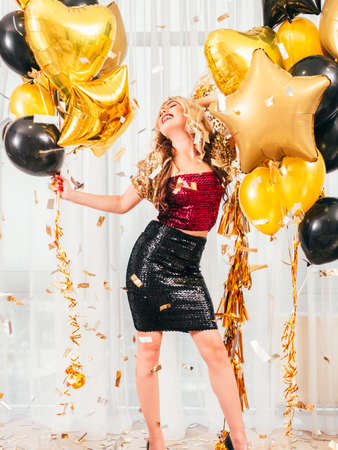 Girls party. Special occasion. Beautiful blonde lady in dressy sparkling outfit smiling, posing with balloons over white curtains.