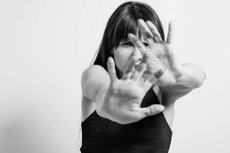 Stop domestic violence. Refusal rejection and denial gesture. Black and white portrait of woman putting palm hand forward