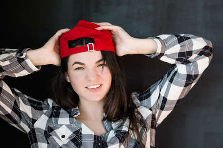 Young woman portrait. Carefree friendly millennial. Red cap casual clothes. Relaxed posture. Warm smile. Hands on head. Stock Photo