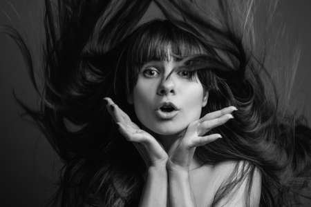 Astounded pretty girl. Black and white portrait of young brunette woman with long hair and bangs. Beauty care.