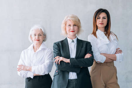 Successful business women. Ambitious female team. Confident mature and young ladies standing with arms folded over light wall. 写真素材
