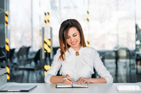 Human resources executive at work. Succesful business woman. Young brunette lady sitting at desk with notebook, smiling. Фото со стока