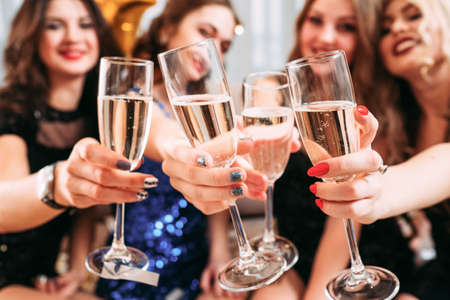 Girls party. Closeup of glasses with champagne. Young ladies celebrating special occasion, having fun together.