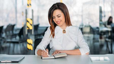 Coaching d'entreprise. Carrière professionnelle réussie. Jeune femme brune assise au bureau en prenant des notes, souriant.