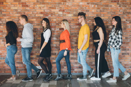 Orderly queue. Millennials moving toward future. Young men women standing in line full length. Anticipation, hope, belief.