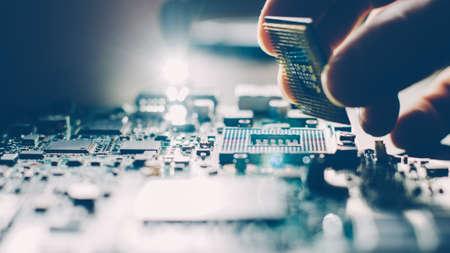 Ingeniero conectando el microprocesador de la CPU al zócalo de la placa base. Mantenimiento o reparación de tecnología informática y hardware. Foto de archivo
