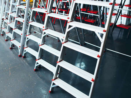 Aluminum extension ladders display. Construction industry products shop. Metal staircase for workers.