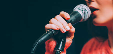 Singer at microphone. Woman singing and holding mic. Female vocal talent. Music show recital. Stockfoto