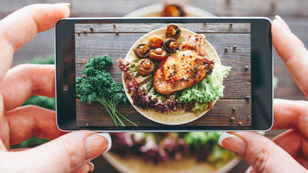 Culinary blog. Home cooking hobby. Food recipe. Closeup of female hands taking picture of roasted meat with grilled mushrooms. Stock fotó